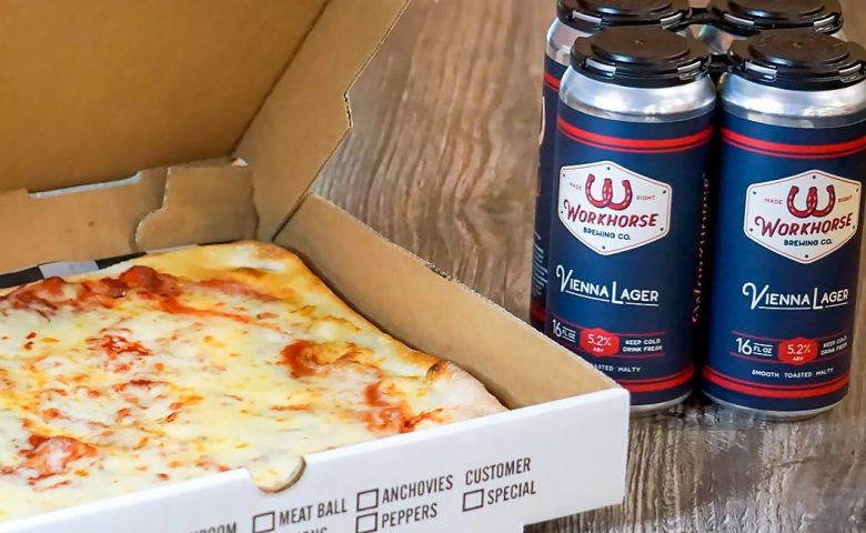 pizza in a box with a six pack of beer beside it
