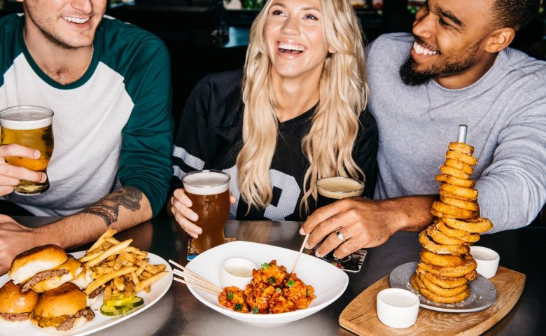 Three people sitting and laughing at a table full of food and beer