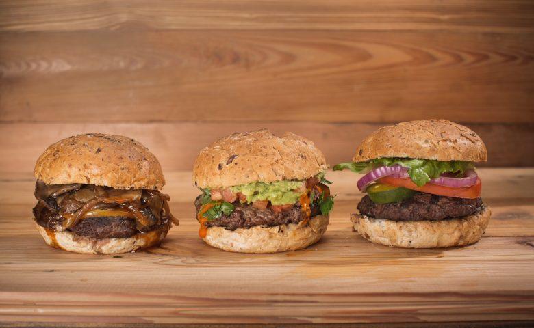 Three hamburgers on a wood table