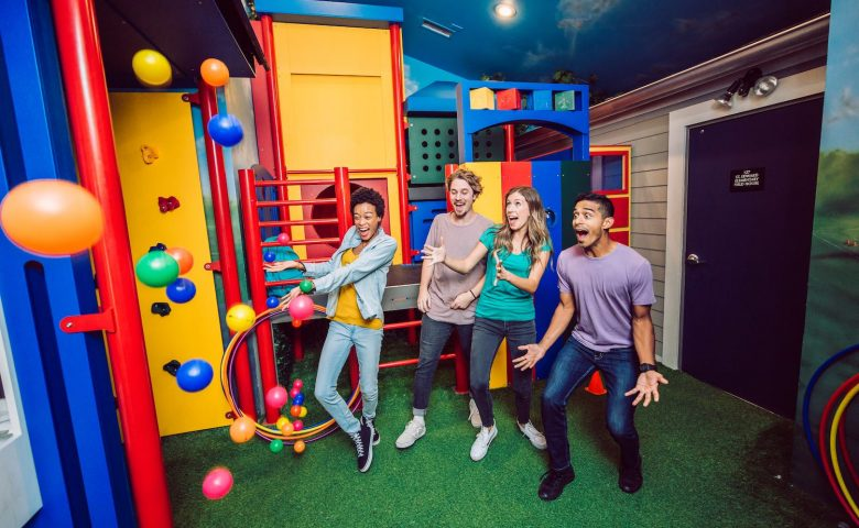 four people in a playground looking surprised as plastic balls fall from the ceiling
