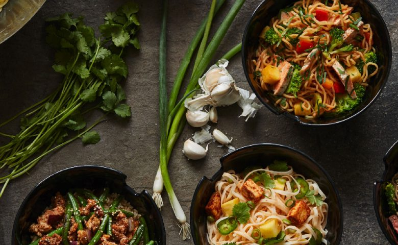 aerial view of four bowls full of different stir fry
