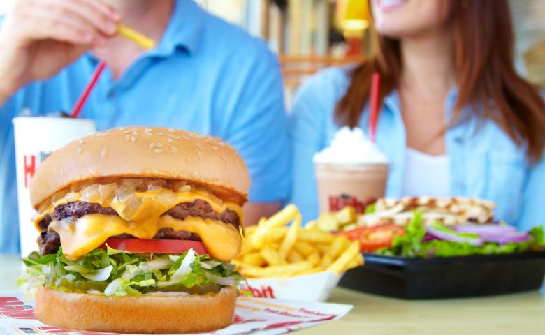 Hamburger with two people and milkshakes in the background