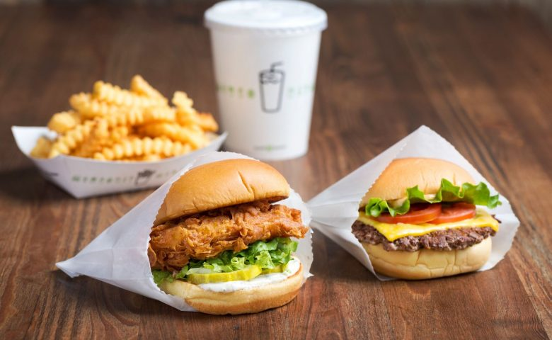 Sandwiches, fries and a drink on a wooden table
