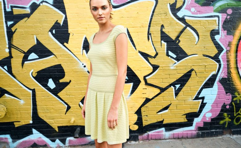 woman in yellow striped dress standing in front of a graffiti wall